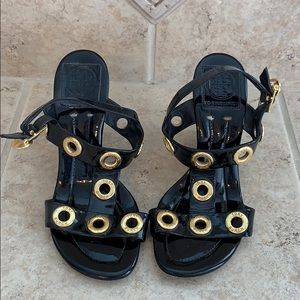 Tory Burch patent leather wedges with gold detail.